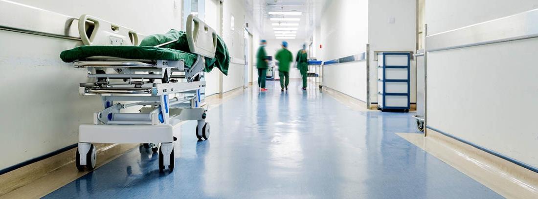 Pasillo de hospital con camilla y personal sanitario al fondo