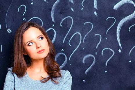 Mujer con cabeza ladeada delante de un fondo negro con signos de interrogación
