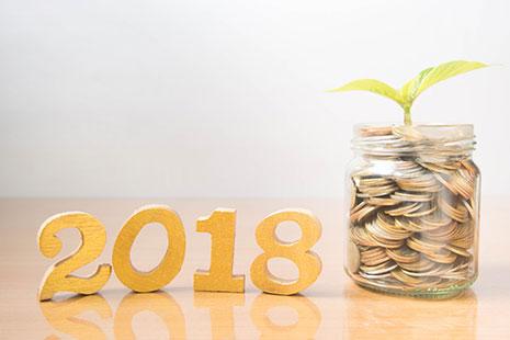 Cifras que conforman 2018 junto a bote de cristal con monedas y planta verde