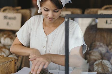 Mujer de blanco con pañuelo en la cabeza y cestos con pan