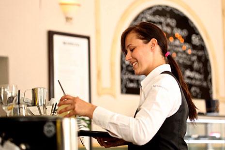 Mujer con camisa blanca y chaleco negro poniendo unos vasos sobre una bandeja
