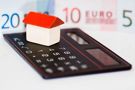 Casa sobre una calculadora y billetes