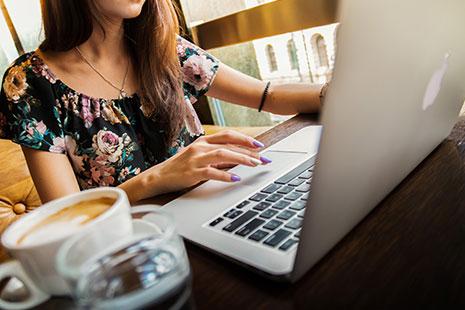 Mujer frente a un ordenador y una taza de café