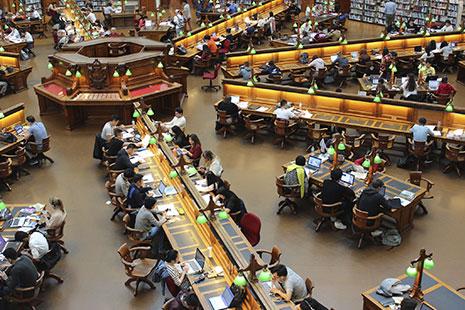 Vista general de muchos hombres y mujeres sentadas en hileras  y estantes con libros