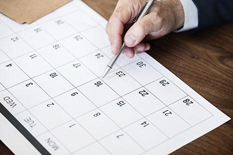Mano con boli sobre un calendario
