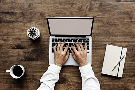 Vista cenital de manos sobre un teclado de ordenador