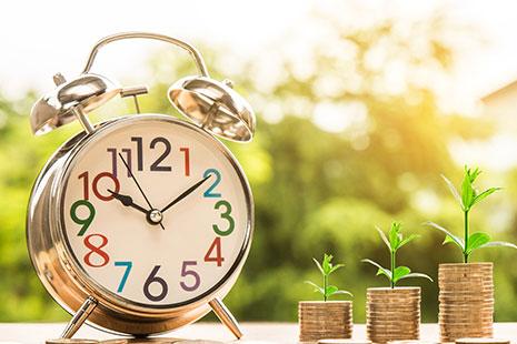 Montañas de dinero al lado de un reloj