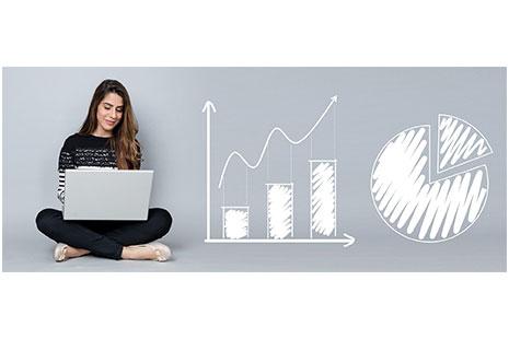 Mujer con ordenador y gráficos detrás