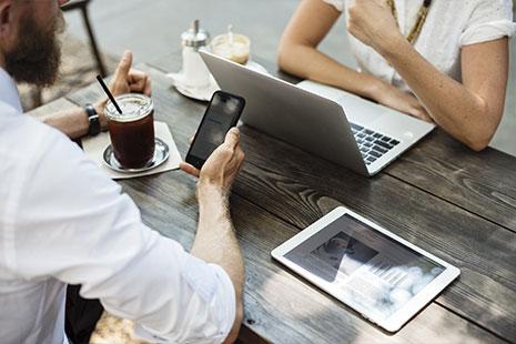 Hombre sujeta móvil sentado frente a él otra persona con un portátil delante