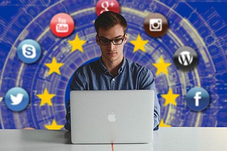 Hombre con gafas detrás de un portátil y fondo de logotipos de redes sociales sobre azul