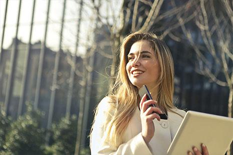 Mujer joven con móvil y tableta en la mano y gesto sonriente