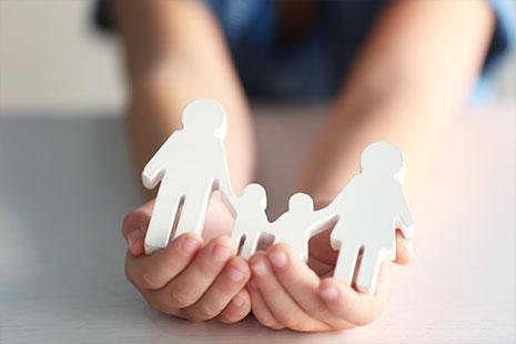 Manos infantiles sujetan sobre ellas figuras blancas de hombre, mujer y niños de la mano