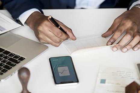 Manos sobre una mesa con papeles y teclado de ordenador