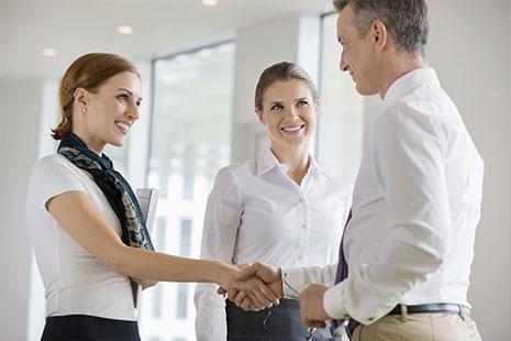 Dos personas estrechándose la mano bajo la atenta mirada de una mujer