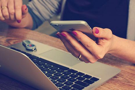 Manos de mujer sujetando un móvil junto a un ordenador