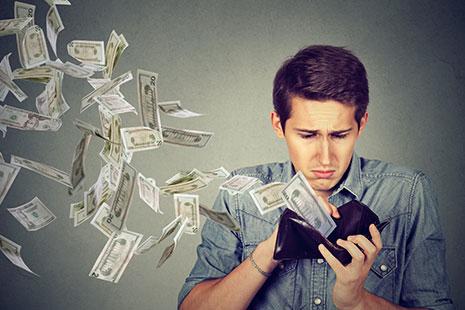 Hombre mirando una billetera y billetes que vuelan