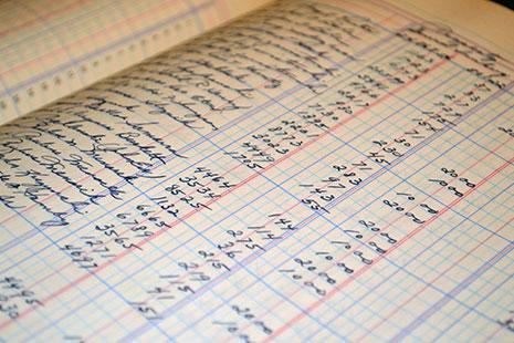 Cuadrícula azul y columnas con líneas rojas con apuntes de números manuscritos