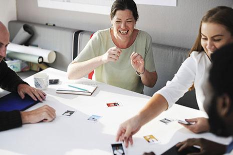 Mujer sonriente sentada junto a otras personas a una mesa con fotos sobre ella
