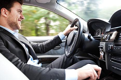 Hombre con traje conduciendo un coche