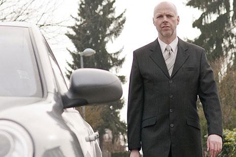 Hombre con traje y maletín junto a un coche