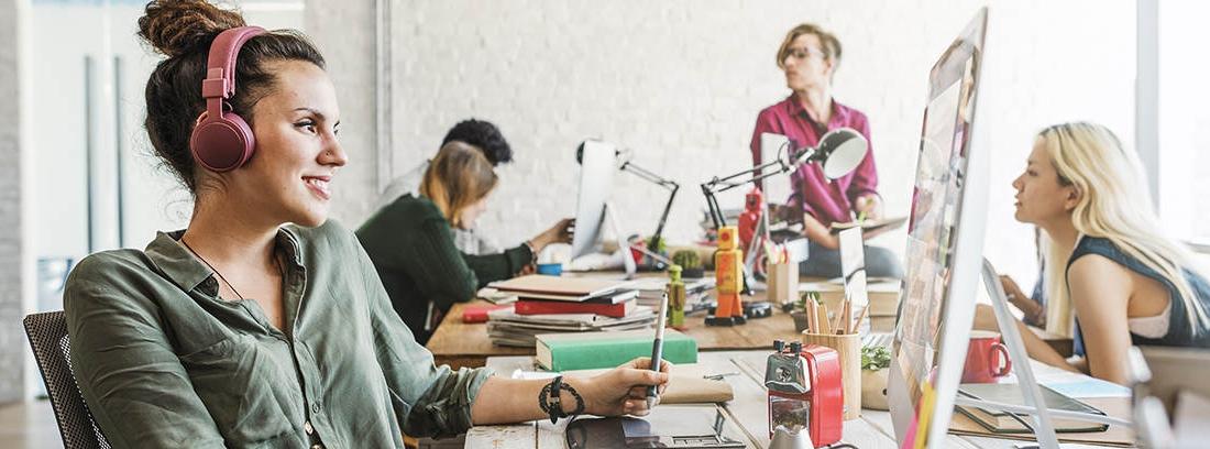 Varias personas con ordenadores y cuadernos en una misma mesa