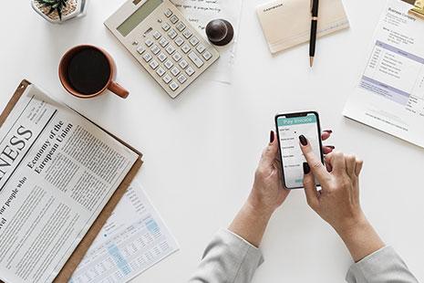 Manos tocando la pantalla de un móvil sobre una mesa con papeles y calculadora