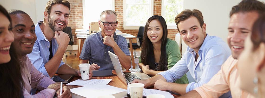 Grupo de hombres y mujeres sonrientes sentados alrededor de una mesa con papeles