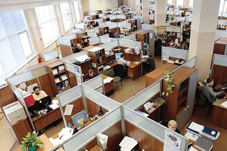 Espacio dividido con paneles con mesas y sillas de trabajo y personas en ellas