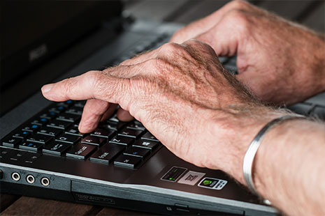 Manos de anciano sobre un teclado de ordenador