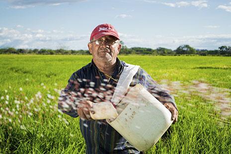 Hombre con gorra roja con un gran recipiente blanco colgado y uno pequeño en la mano
