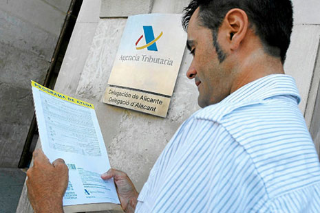 Hombre mirando papeles delate de un letrero de la Agencia Tributaria