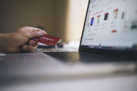 Mano sujeta tarjeta de pago roja delante de pantalla de ordenador portátil