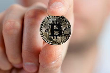 Dedos sujetando un bitcoin