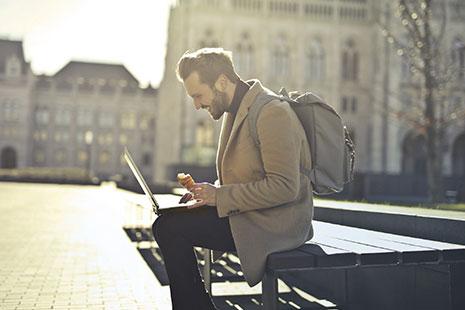 Hombre con mochila y abrigo sentado sostiene sobre sus rodillas portátil abierto