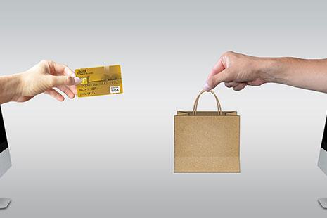 Pantalla de ordenador de la que sale una mano con una tarjeta de crédito dirigida hacia otra mano con una bolsa de papel que sale de otra pantalla