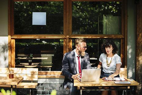 Hombre con corbata roja y gafas sentado delante de portátil y junto a mujer con agenda