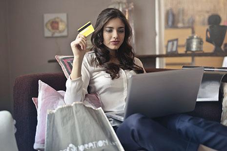 Mujer sentada en sofá con tarjeta de pago amarilla en la mano y portátil sobre las rodillas
