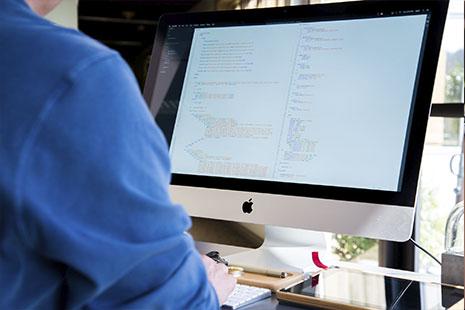 Pantalla de ordenador con fondo blanco y código en colores delante una persona