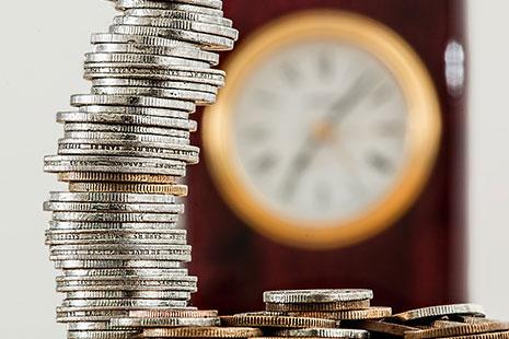 Columna de monedas con reloj al fondo