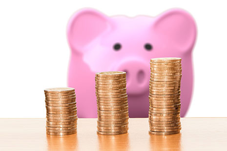 Tres columnas de monedas con una hucha de cerdo al fondo