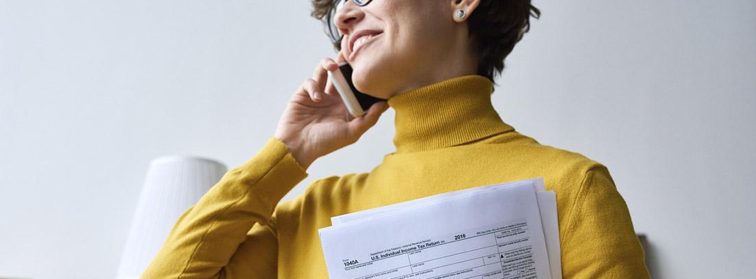 mujer con jersey amarillo hablando por teléfono con papeles de la declaración de la renta