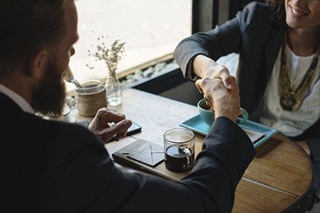 Hombre y mujer estrechan sus manos sobre una mesa con tazas
