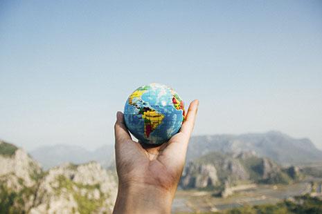 Mano sujeta una esfera con fondo azul y dibujos de países de colores