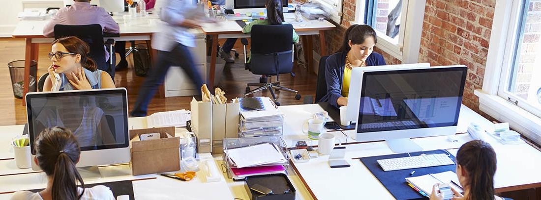 Oficina con mesas, ordenadores y personas