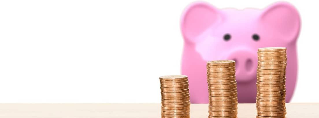 Hucha de cerdo detrás de unas columnas de monedas