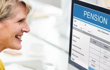 Mujer sonriente consultando las ventajas de su plan de pensiones en un ordenador