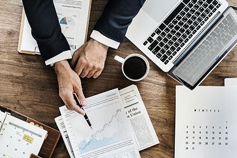 Manos de hombre apuntando con un boli en un papel en el que se ve un gráfico, sobre una mesa con ordenador, calendarios, agenda, papeles y taza de café