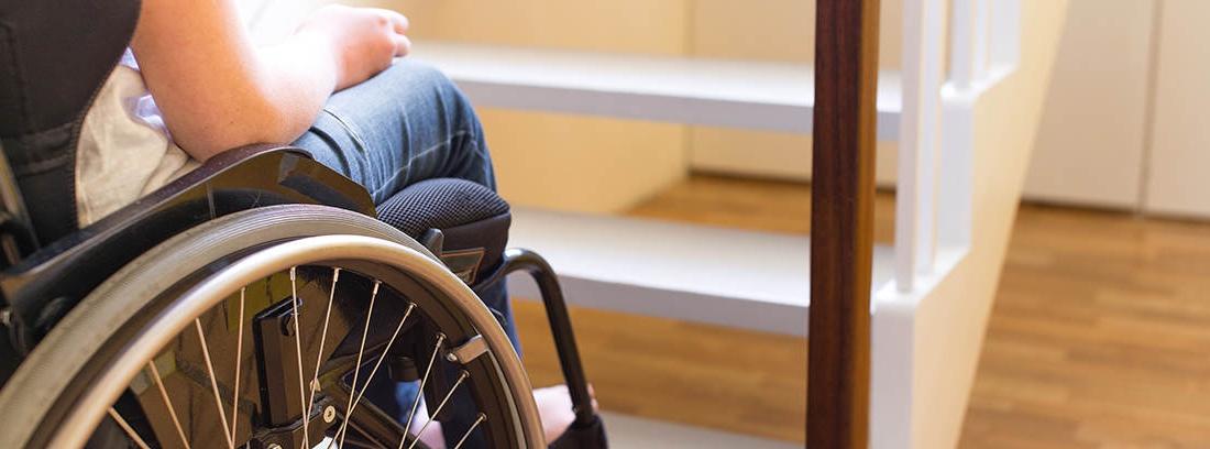 Persona en silla de ruedas frente a una escalera