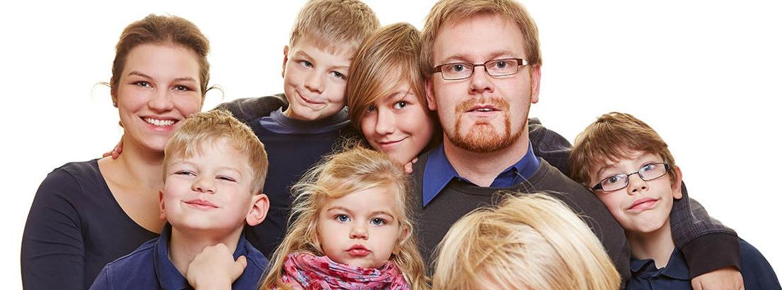 Mujer y hombre rodeados de seis niños de diferentes edades