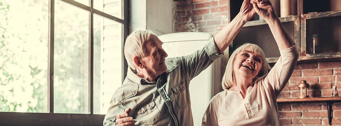 Pareja de ancianos bailando en una cocina con dos verduras  y dos copas de vino sobre la mesa